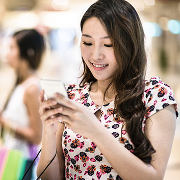 Mobile Shopping: Asiatin mit Smartphone