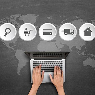 Online shopping icons and laptop in front of world map
