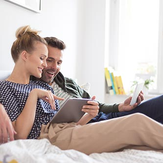 Couple sitting on a couch while shopping online with a tablet