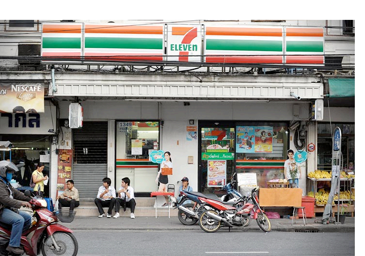 Street view and people sitting in front of a 7eleven store in Asia